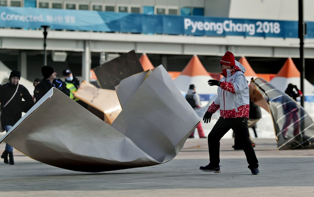A volunteer chases down solar film backing that blew off the Coca-Cola building inside Gangneung Olympic Park at the 2018 Winter Olympics in Gangneung