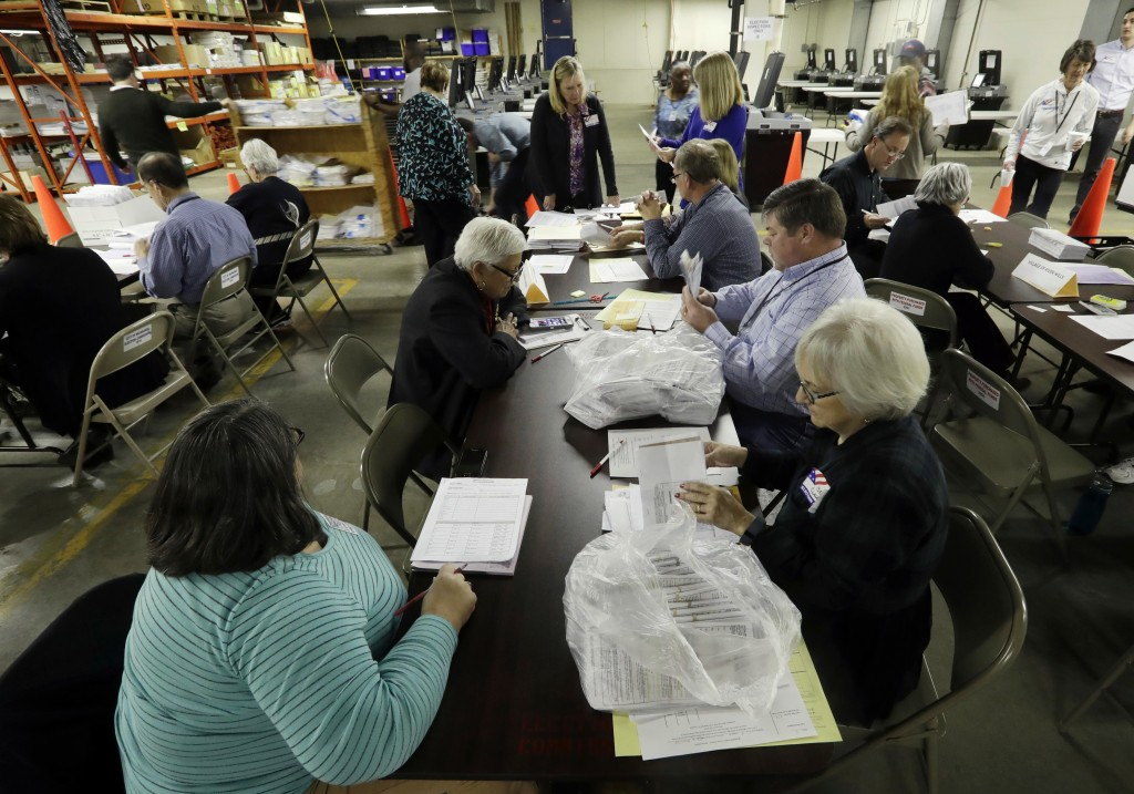 FILE- In this Dec. 1, 2016, file photo, workers begin a statewide presidential election recount in Milwaukee. Since last July, a bipartisan team at Ha