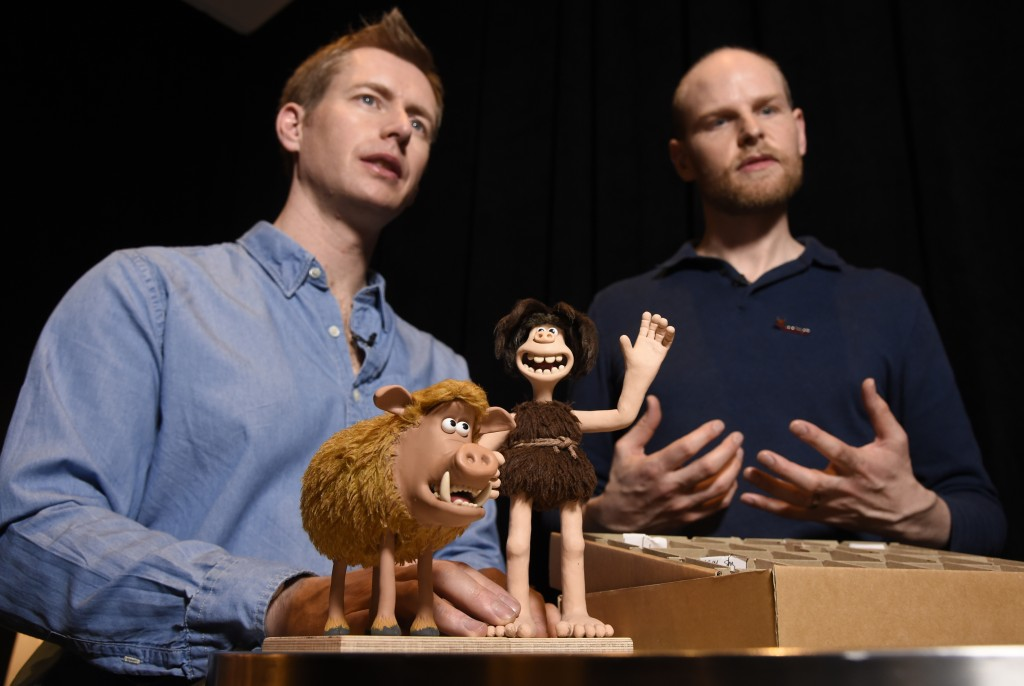 "In this Feb. 8, 2018 photo, Merlin Crossingham, left, and Will Becher, animation directors for the stop-motion animated film ""Early Man,"" discuss the"