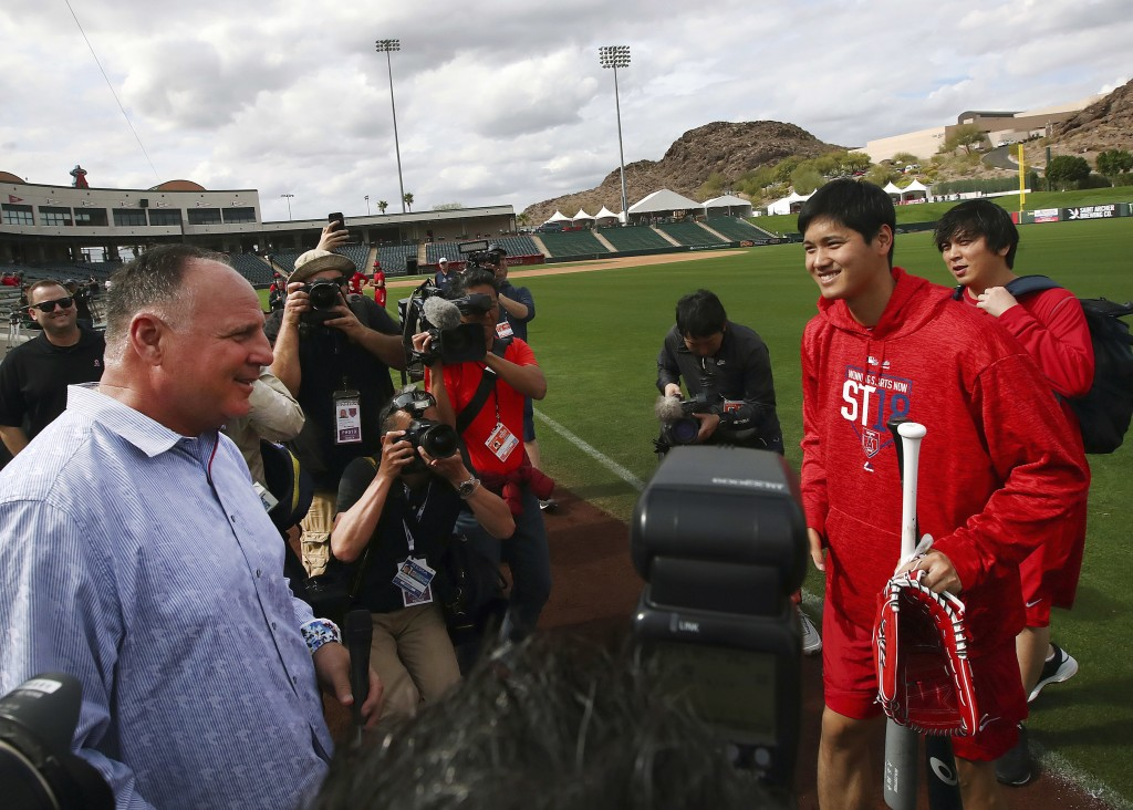 Los Angeles Angels' Shohei Ohtani, second from right holding bat, speaks with coach Mike Scioscia during a spring training baseball practice on Tuesda