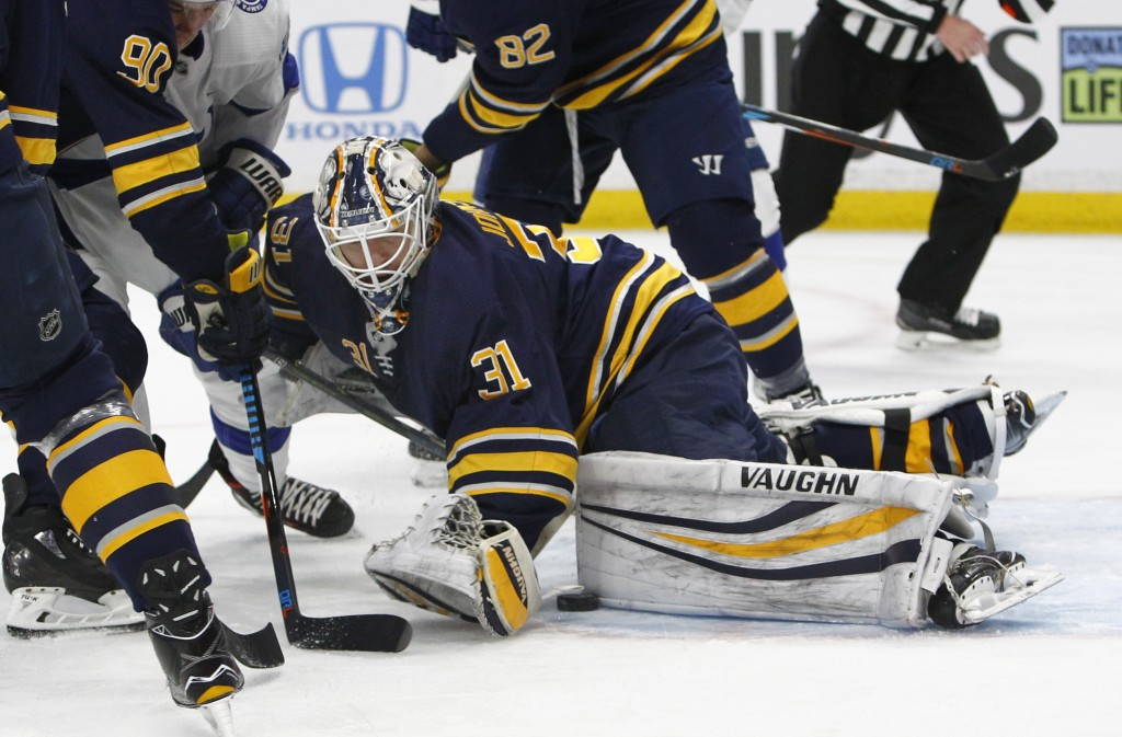 Buffalo Sabres goalie Chad Johnson (31) tries to cover the puck during the first period of the team's NHL hockey game against the Tampa Bay Lightning,