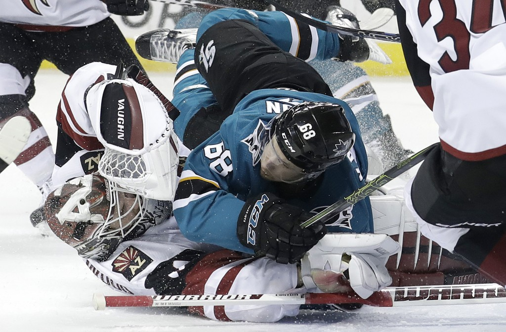 San Jose Sharks right wing Melker Karlsson, from Sweden, top, crashes into Arizona Coyotes goaltender Scott Wedgewood during the second period of an N
