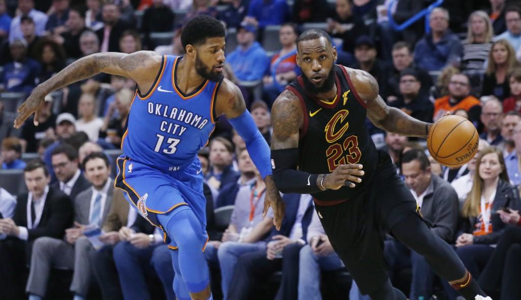 Cleveland Cavaliers forward LeBron James (23) drives past Oklahoma City Thunder forward Paul George (13) during the first half of an NBA basketball ga