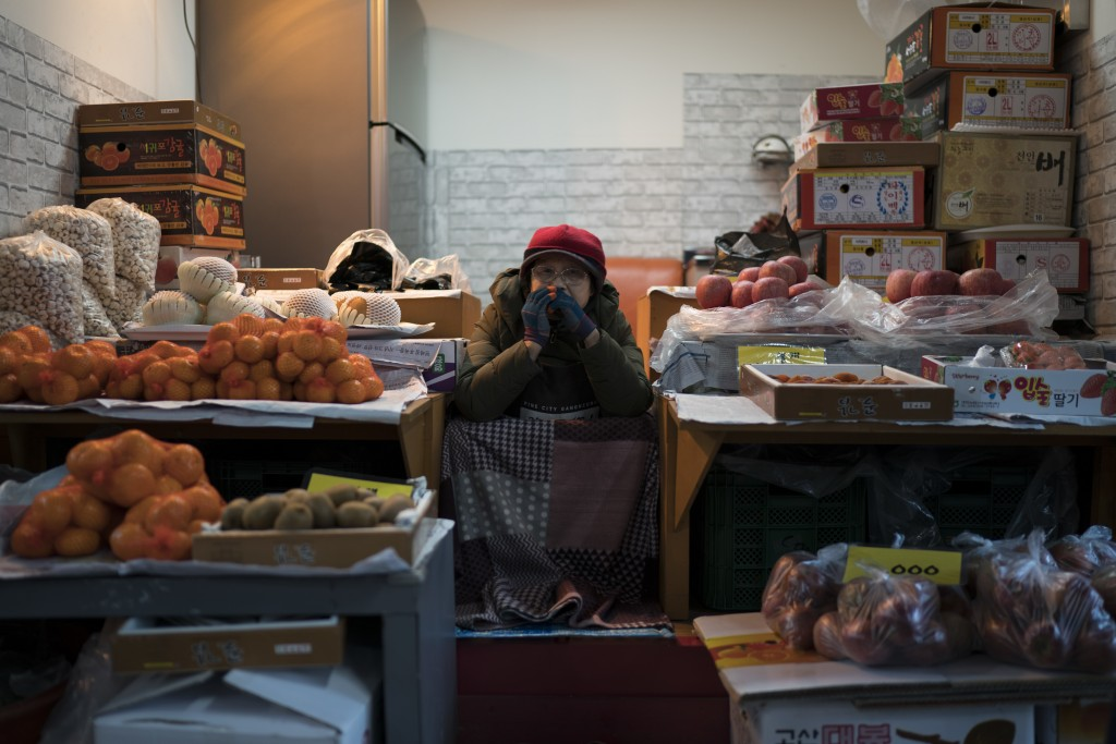 A woman selling fruits waits for costumers at the traditional market in Gangneung, South Korea, Monday, Feb. 12, 2018. One part of the Pyeongchang are