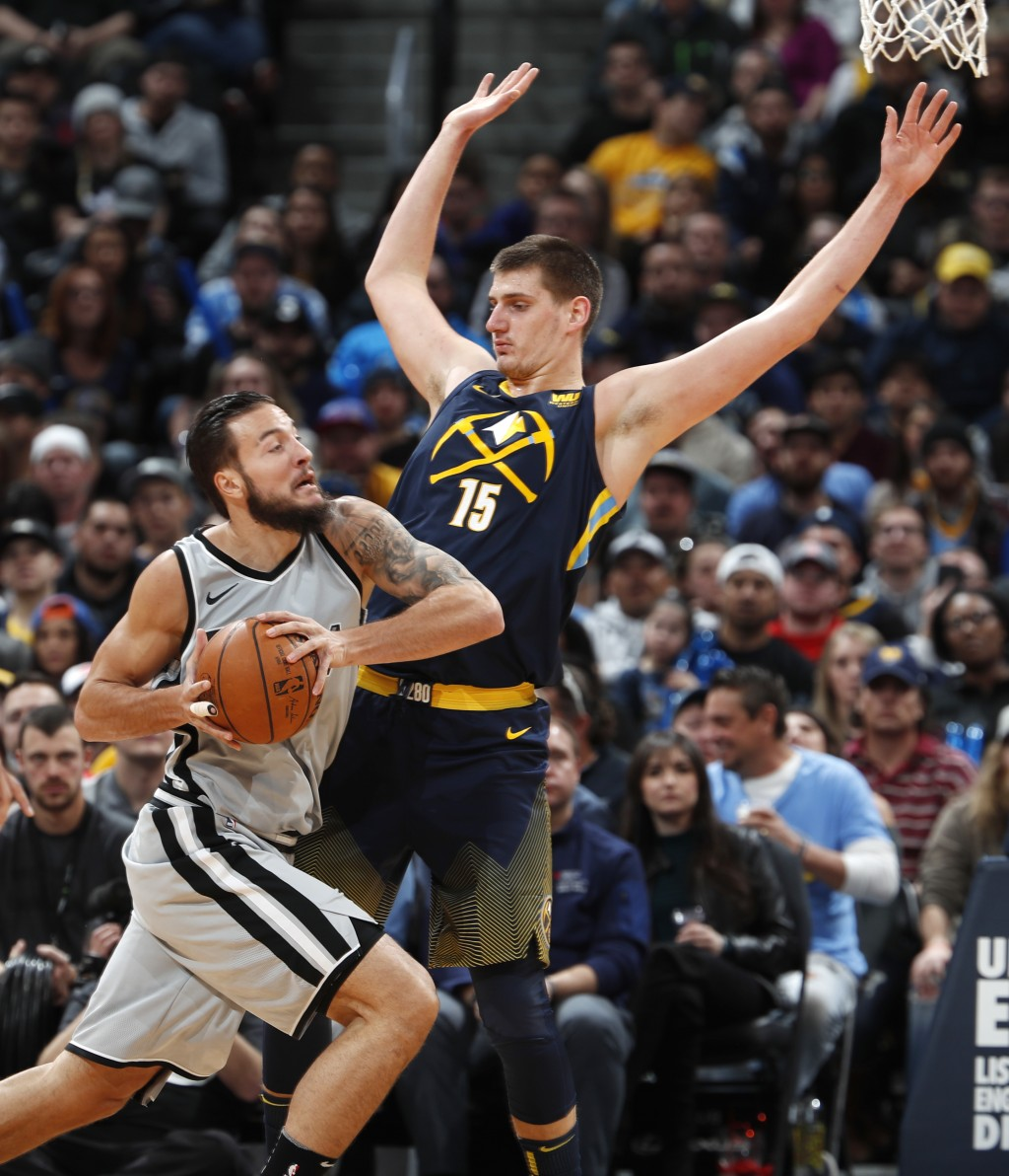 San Antonio Spurs center Joffrey Lauvergne, left, drives against Denver Nuggets center Nikola Jokic on the way to to the basket during the first half