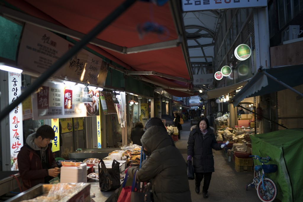 People shop at the traditional market in Gangneung, South Korea, Tuesday, Feb. 13, 2018. Markets like this one are a common sight in South Korea. And