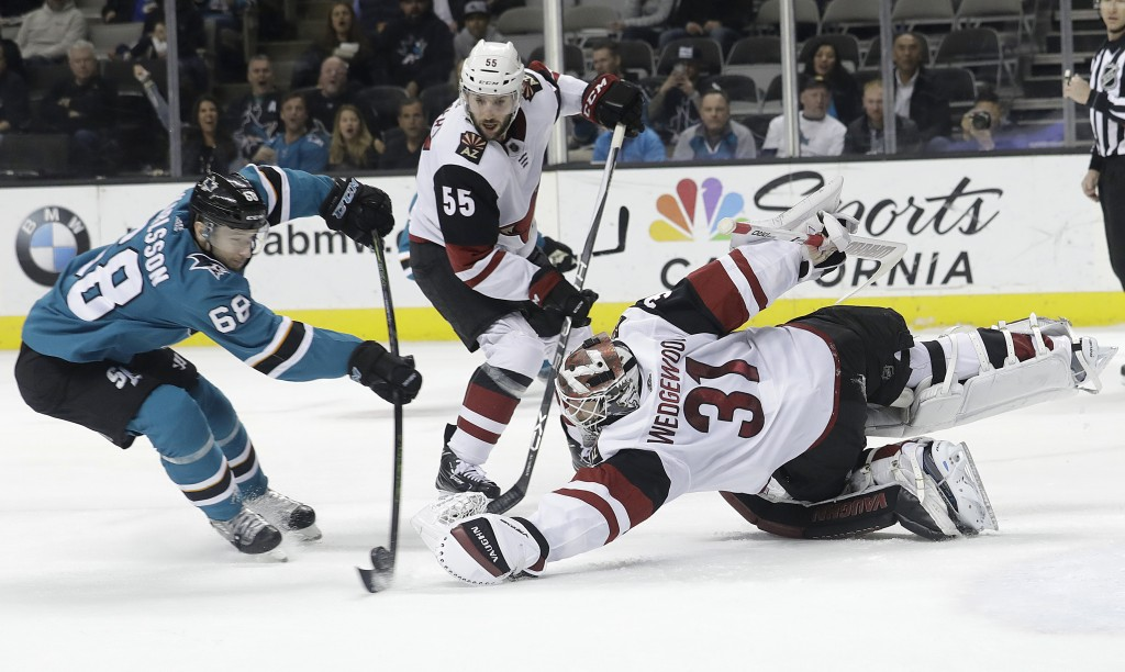 Arizona Coyotes goaltender Scott Wedgewood (31) reaches for the puck in front of San Jose Sharks right wing Melker Karlsson (68), from Sweden, during