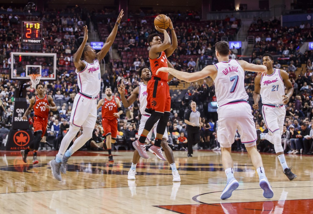 Toronto Raptors' Kyle Lowry puts up a shot against Miami Heat, left to right, Josh Richardson, Goran Dragic, and Hassan Whiteside during the first hal