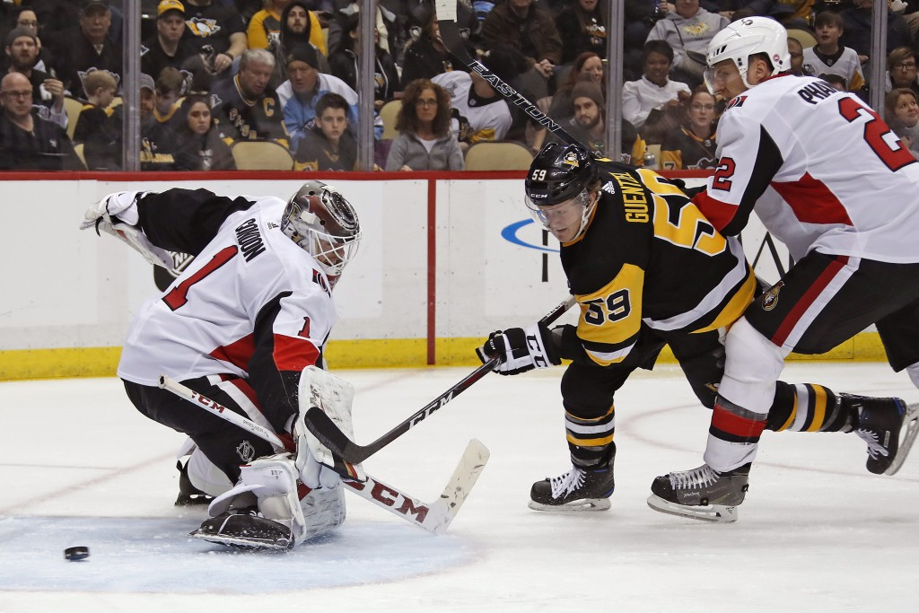 Pittsburgh Penguins' Jake Guentzel (59) gets a shot past Ottawa Senators goaltender Mike Condon (1) for a goal with Dion Phaneuf (2) defending during