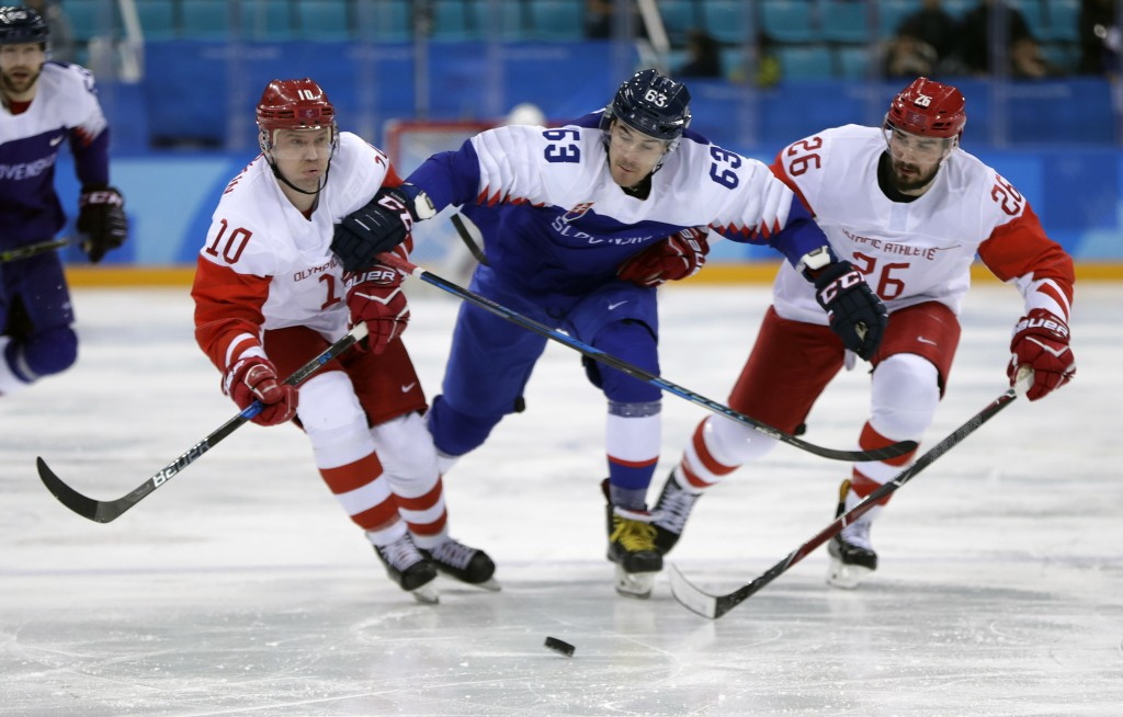 Patrik Lamper (63), of Slovakia, battles for the puck against Russian athletes Sergei Mozyakin (10) and Vyacheslav Voinov (26) during the third period