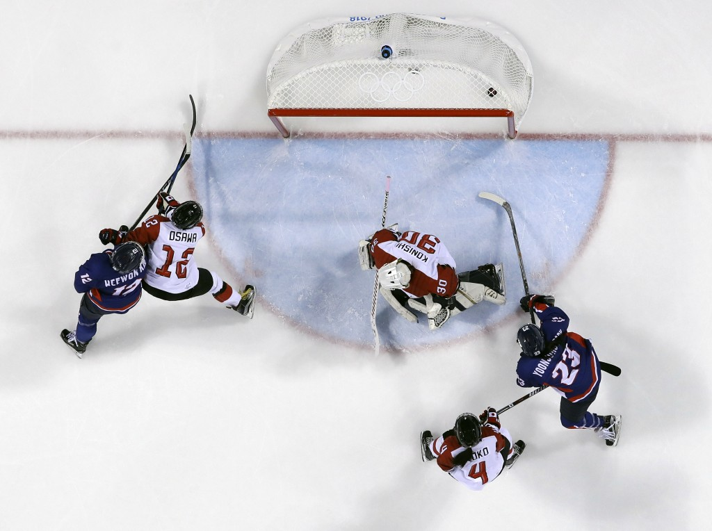 The puck shot by South Korea's Randi Heesoo Griffin (37), of the combined Koreas team, sails past goalie Akane Konishi (30), of Japan, during the seco