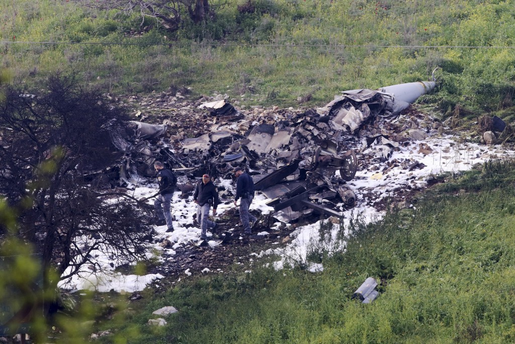 FILE - This Saturday, Feb. 10, 2018 file photo, shows Israeli security oficers at the wreckage of an F-16 that crashe, near the Harduf kibbutz, in nor