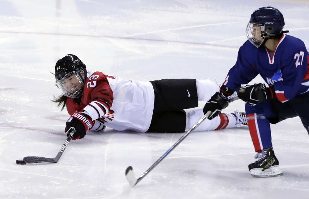 Ami Nakamura (23), of Japan, tries to control the puck against North Korea's Jong Su Hyon (27), of the combined Koreas team, as she falls during the s