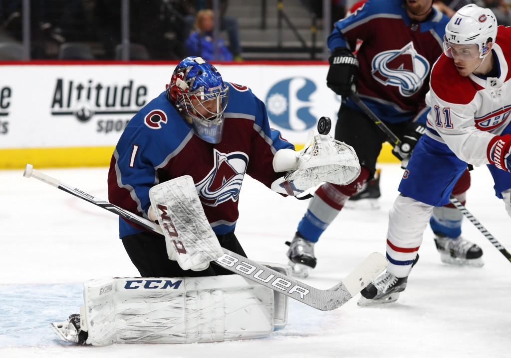 Colorado Avalanche goaltender Semyon Varlamov, left, makes a glove save of a redirected shot off the stick of Montreal Canadiens right wing Brendan Ga