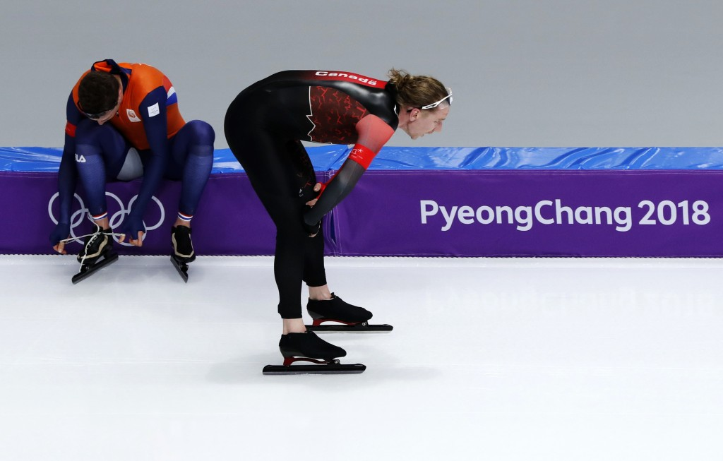 Gold medallist Ted-Jan Bloemen of Canada passes Sven Kramer of The Netherlands who ties his skates for his race on the men's 10,000 meters speedskatin