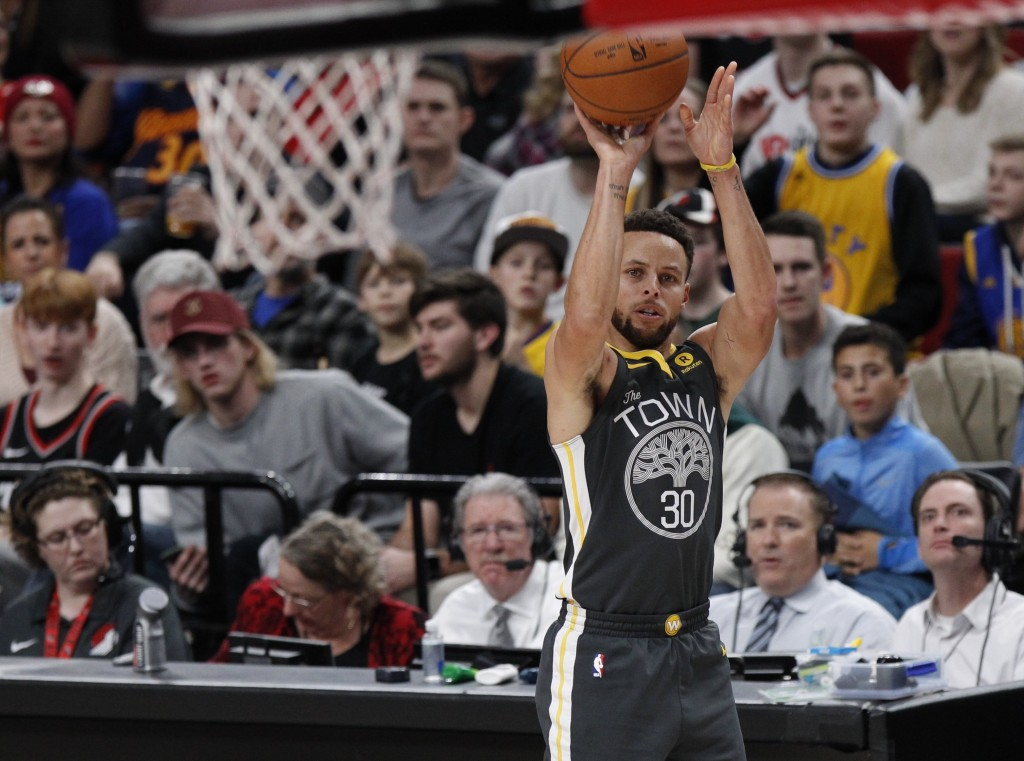 Golden State Warriors guard Stephen Curry takes an open jump shot against the Portland Trail Blazers during the first half of an NBA basketball game i
