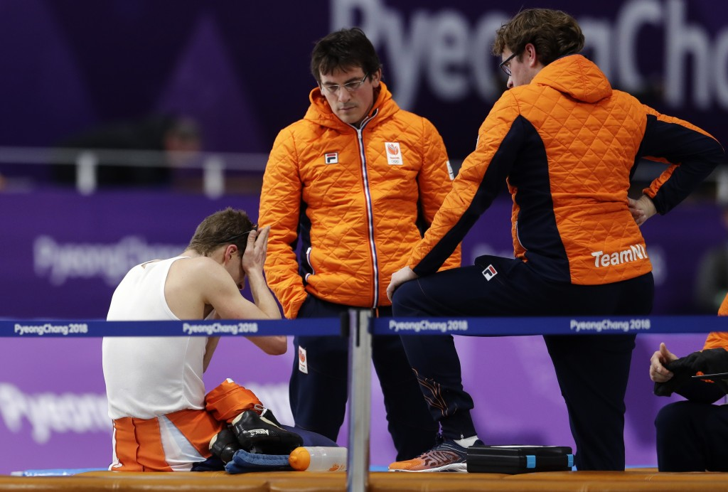 Sven Kramer of The Netherlands, left, reacts as he sits with his coaches after his performance on the men's 10,000 meters speedskating race at the Gan