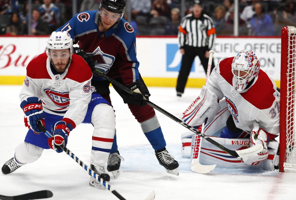 From left, Montreal Canadiens defenseman Victor Mete looks to stop a pass intended for Colorado Avalanche center Tyson Jost as Montreal goaltender Ant