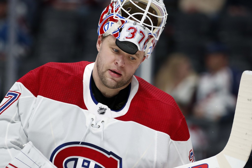 Montreal Canadiens goaltender Antti Niemi pulls up his helmet during a time out against the Colorado Avalanche in the first period of an NHL hockey ga