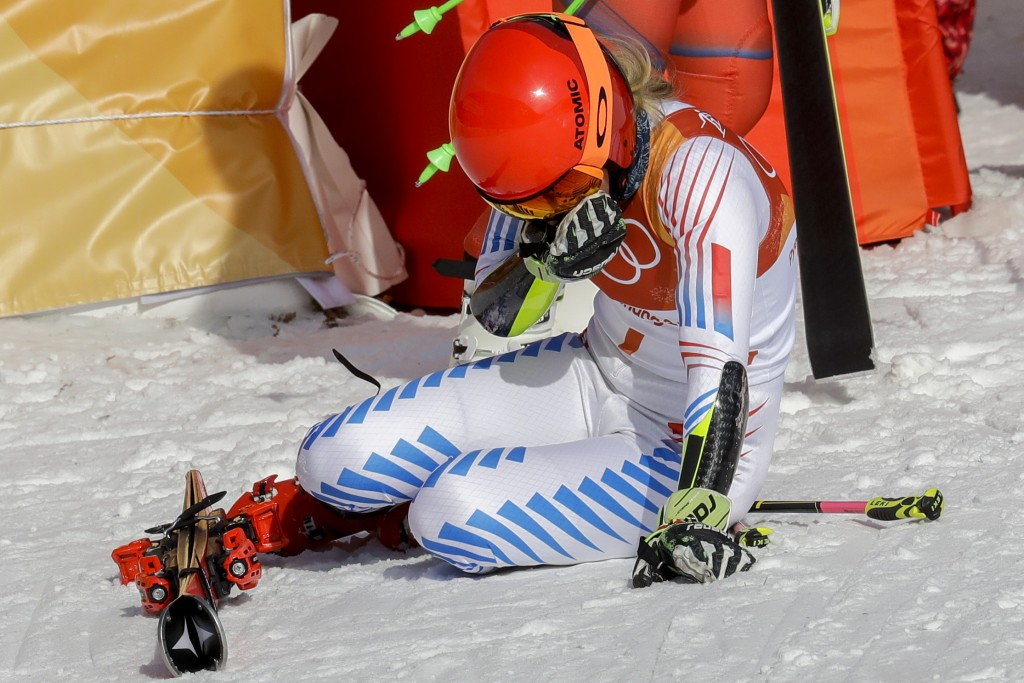 Mikaela Shiffrin, of the United States, falls to her knees after winning the gold medal in the Women's Giant Slalom at the 2018 Winter Olympics in Pye