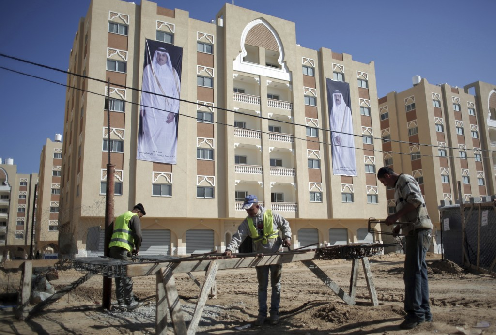 FILE - In this Jan. 16, 2016 photo, Palestinians work at the Qatari-funded Hamad City housing complex in Khan Younis, southern Gaza Strip. Four years