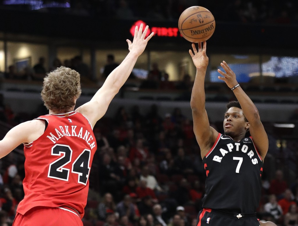 Toronto Raptors guard Kyle Lowry, right, shoots against Chicago Bulls forward Lauri Markkanen during the first half of an NBA basketball game Wednesda