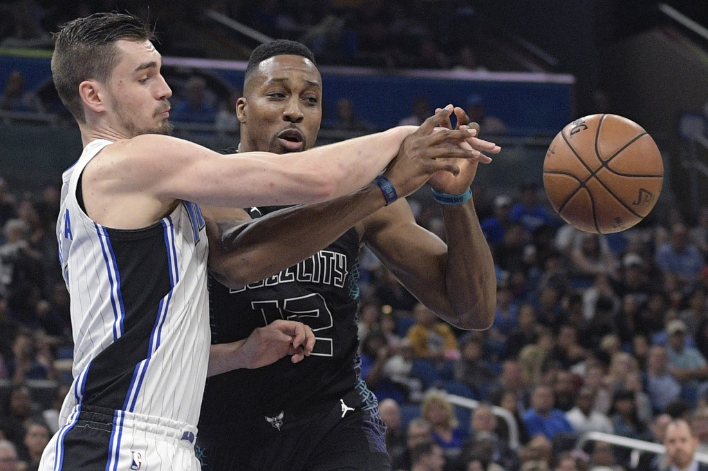 Orlando Magic guard Mario Hezonja, left, strips the ball away from Charlotte Hornets center Dwight Howard (12) during the first half of an NBA basketb