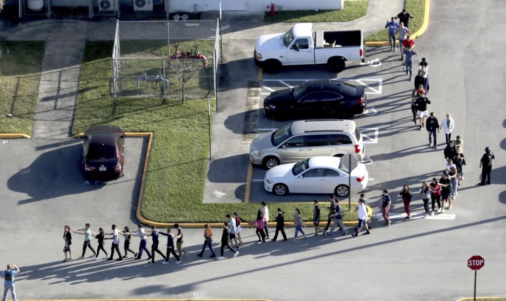 CORRECTS SPELLING TO MARJORY NOT MARJORIE Students are evacuated by police from Marjory Stoneman Douglas High School in Parkland, Fla., on Wednesday,