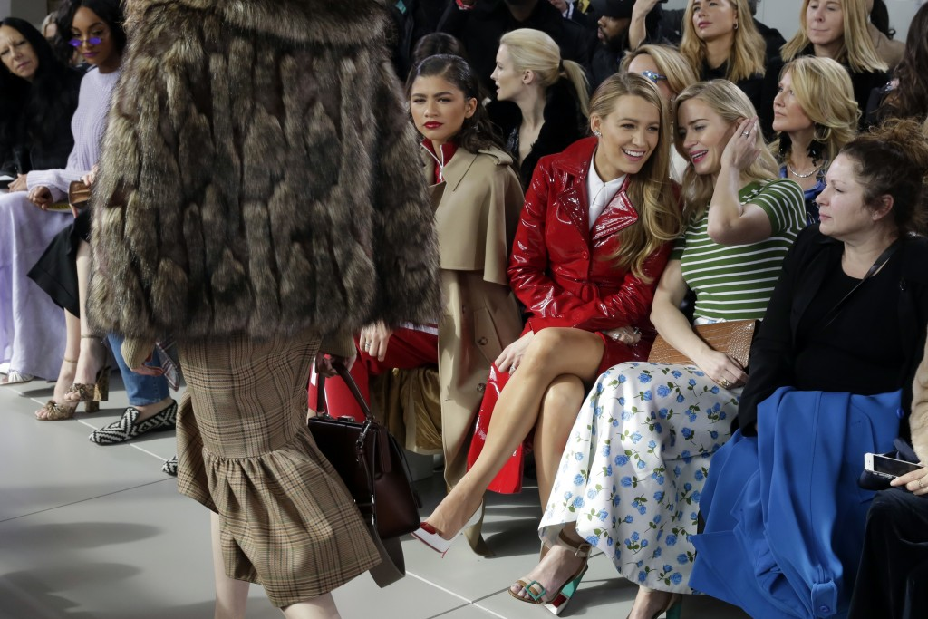 Blake Lively, third from right and Emily Blunt, second from right, talk as the Michael Kors collection is shown during Fashion Week in New York, Wedne
