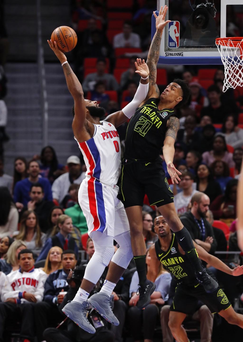 Detroit Pistons center Andre Drummond (0) drives on Atlanta Hawks forward John Collins (20) in the first half of an NBA basketball game in Detroit, We