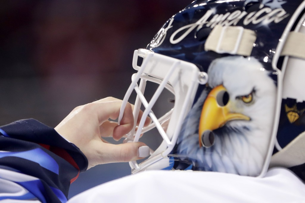 United States goalie Maddie Rooney adjusts her mask during the first period of a preliminary round during a women's hockey game against Canada at the