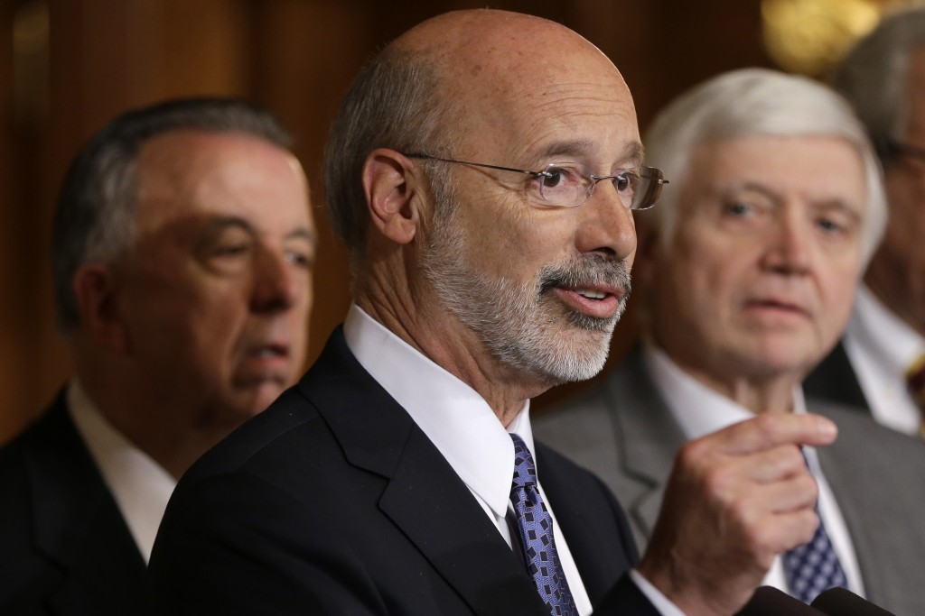 FILE - In this Oct. 7, 2015, file photo, Pennsylvania Gov. Tom Wolf, center, accompanied by state House Minority Leader Rep. Frank Dermody, right, D-A