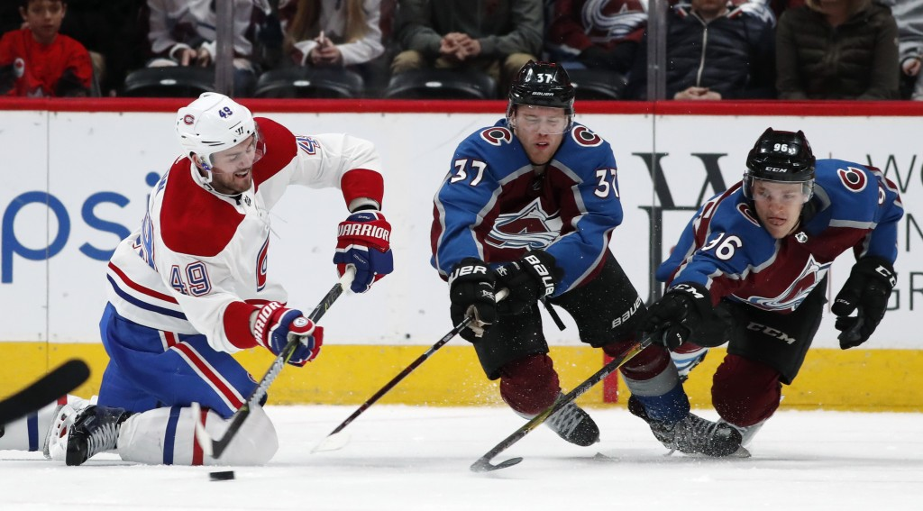 Montreal Canadiens right wing Logan Shaw, left, fires the puck past Colorado Avalanche left wing J.T. Compher, center, and right wing Mikko Rantanen i