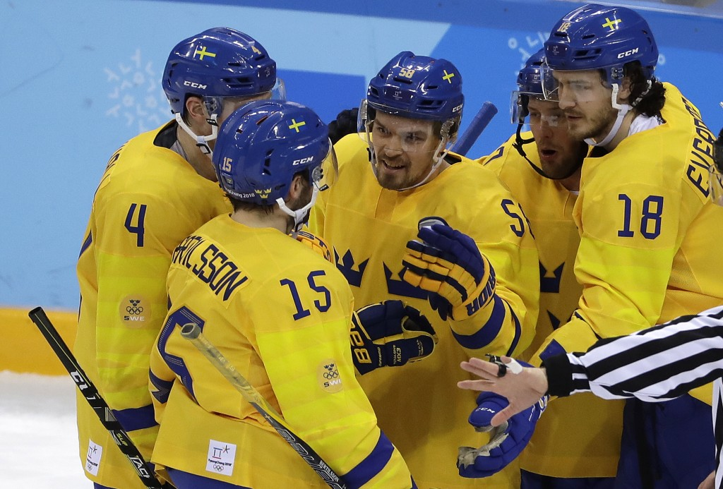 Anton Lander, third from left, of Sweden, talks to his teammates after scoring a goal against Norway during the first period of the preliminary round
