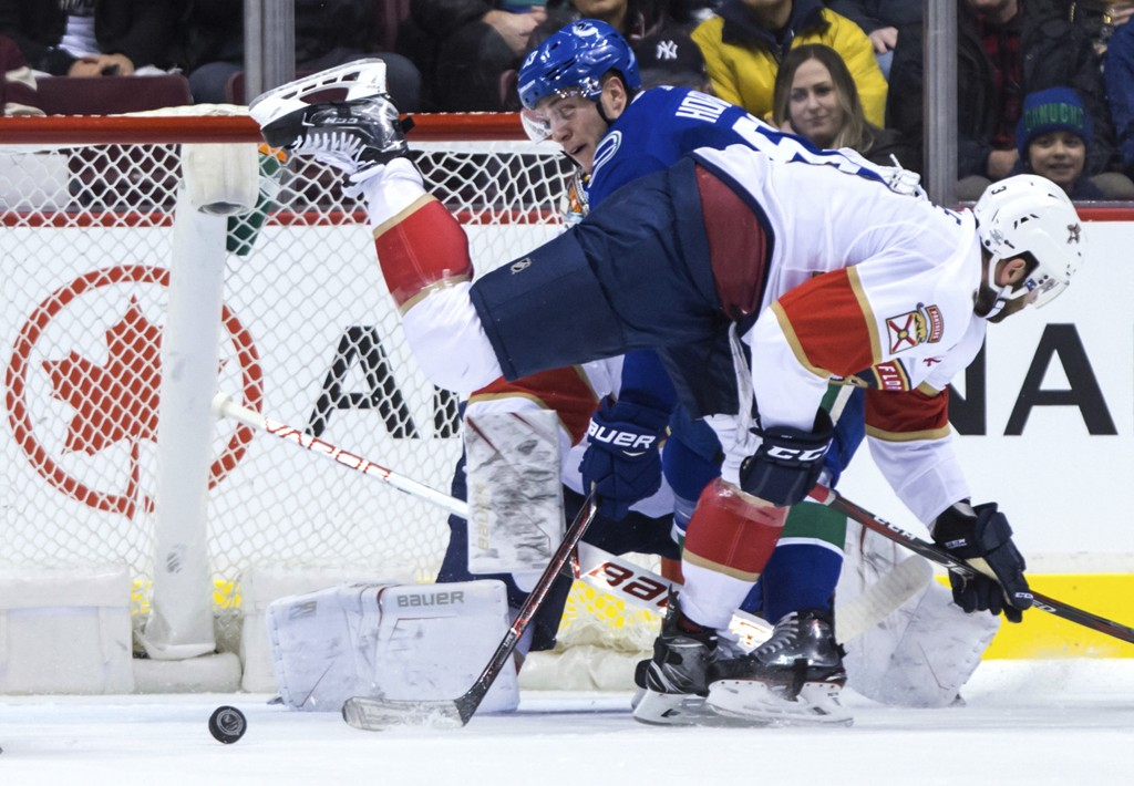 Vancouver Canucks' Bo Horvat, back, tries to get his stick on the puck as Florida Panthers' Keith Yandle, front, defends after goalie James Reimer mad