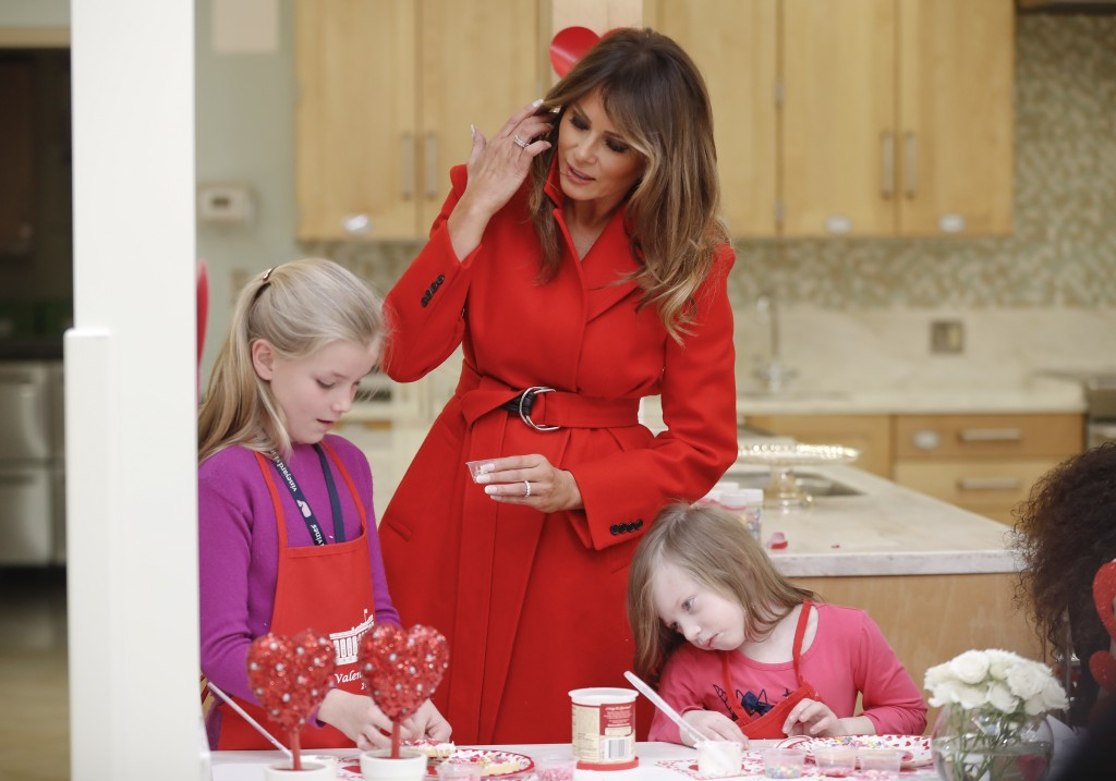 First lady Melania Trump helps Annie Ribas, 9, left, and Katherine Faughn, 6, right, decorate cookies during her visit to the Children's Inn at the Na