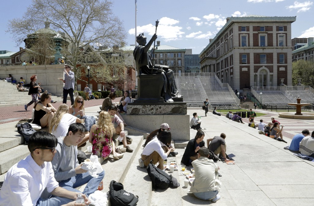 FILE - In this April 29, 2015 file photo, students sit on the steps of Columbia University's Low Memorial Library next to Daniel Chester French's scul