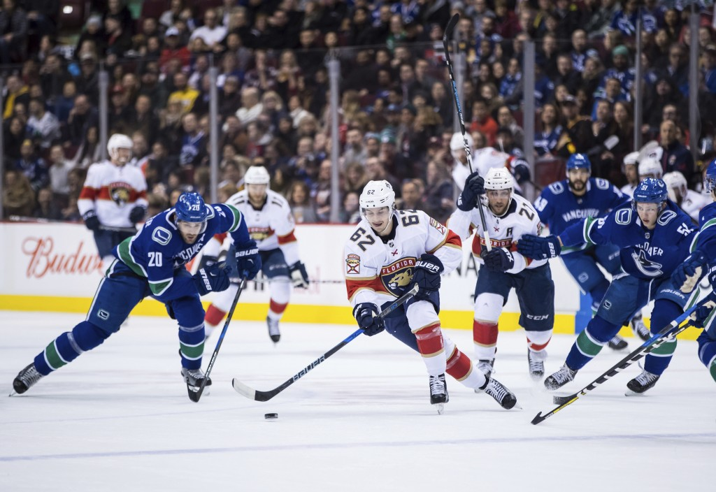 Florida Panthers' Denis Malgin, center, of Switzerland, skates with the puck as Vancouver Canucks' Brandon Sutter (20) and Troy Stecher (51) watch dur