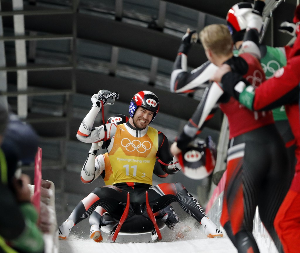 Alex Gough, in red, Sam Edney, in green, Tristan Walker and JustinSnith of Canada react in the finish area after Canada won the silver medal in the l