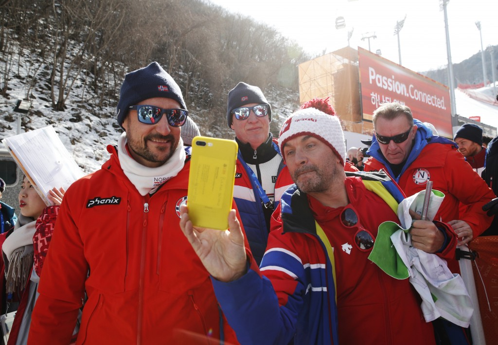 Crown Prince Haakon of Norway, left, takes a selfie with a fan after the men's downhill at the 2018 Winter Olympics in Jeongseon, South Korea, Thursda