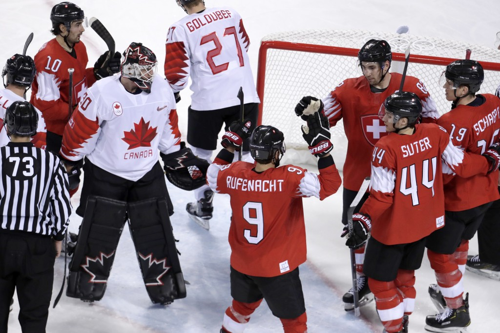 Switzerland players, right, celebrate a goal by Simon Moser, third from right, as Canada goalie Ben Scrivens (30) looks on during the third period of