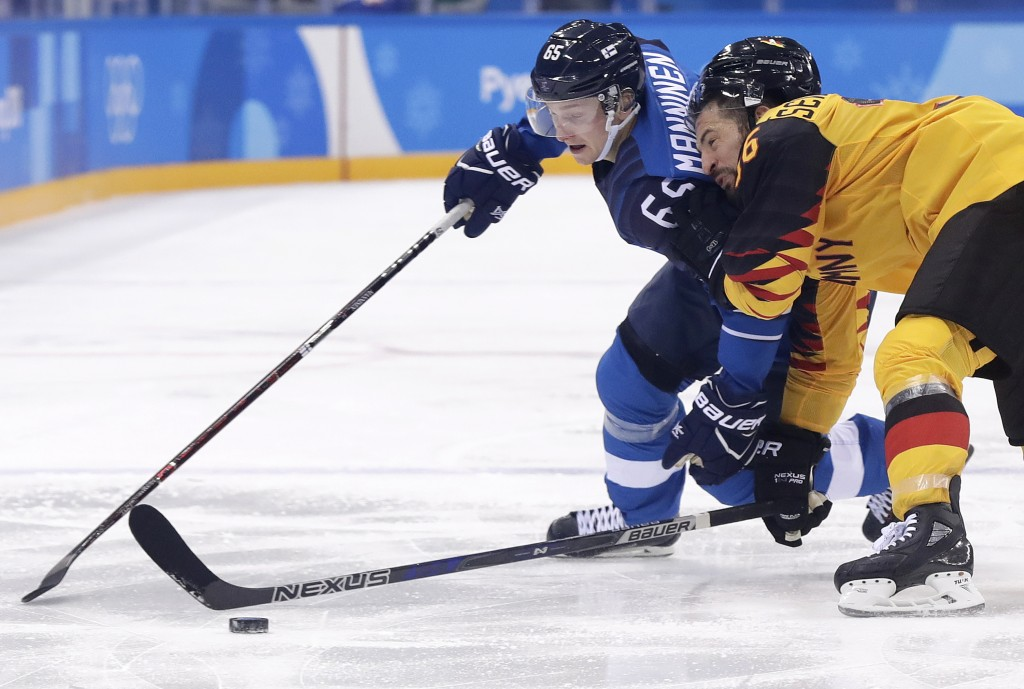 Sakari Manninen (65), of Finland, and Yannic Seidenberg (36), of Germany, battle for the puck during the third period of the preliminary round of the