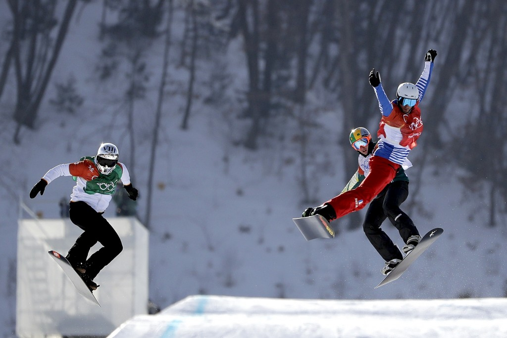 From left; Regino Hernandez, of Spain, Jarryd Hughes, of Australia, and Pierre Vaultier, of France, run the course during the men's snowboard cross fi
