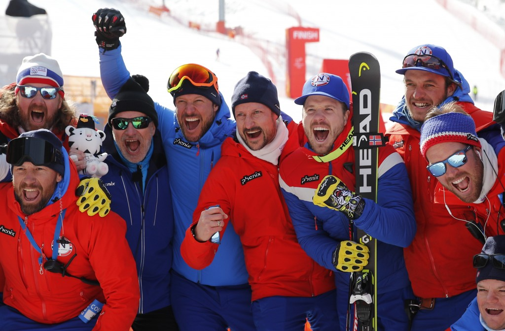 Crown Prince Haakon of Norway, center, poses for photos flanked by Norway's Aksel Lund Svindal, gold, left, and Norway's Kjetil Jansrud, silver, right