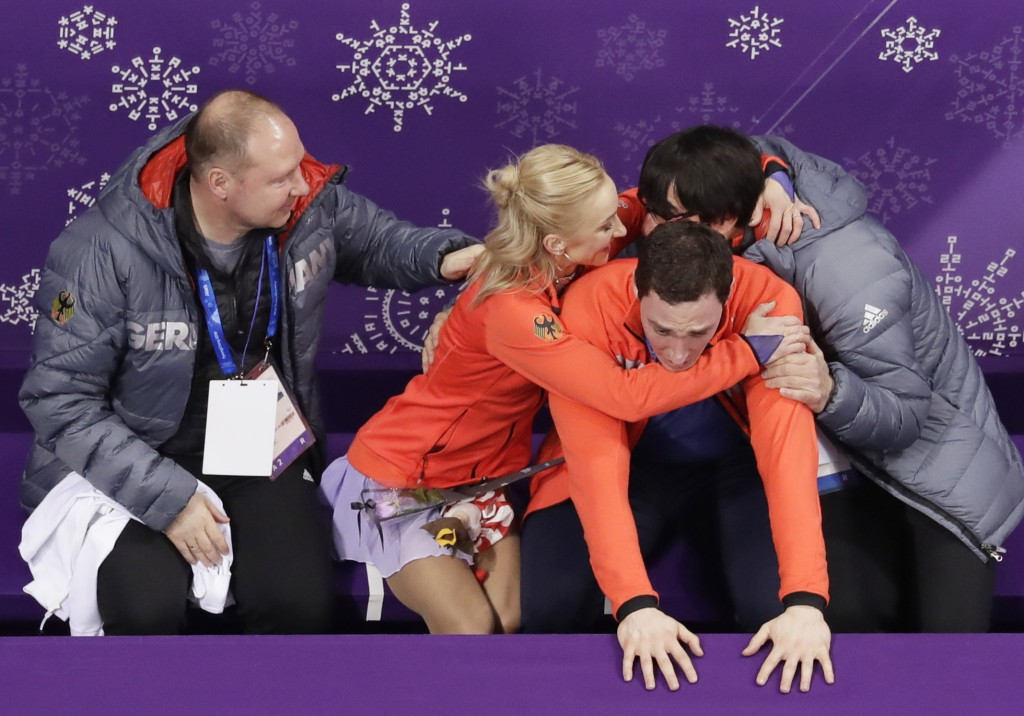 Aljona Savchenko, second left, and Bruno Massot, second right, of Germany react as they receive their scores following their performance in the pairs