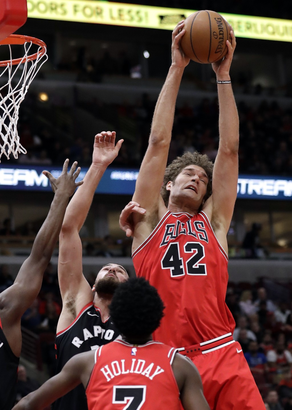 Chicago Bulls center Robin Lopez, right, rebounds a ball against Toronto Raptors center Jonas Valanciunas during the first half of an NBA basketball g