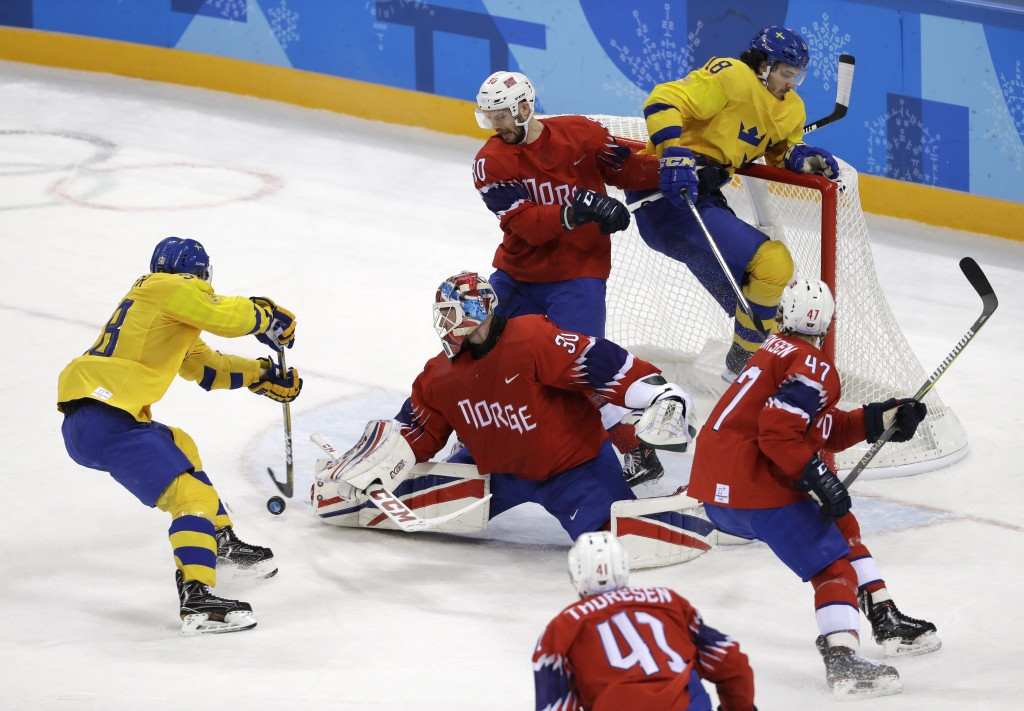 Anton Lander, left, of Sweden, shoots a goal against Lars Haugen (30), of Norway, during the first period of the preliminary round of the men's hockey