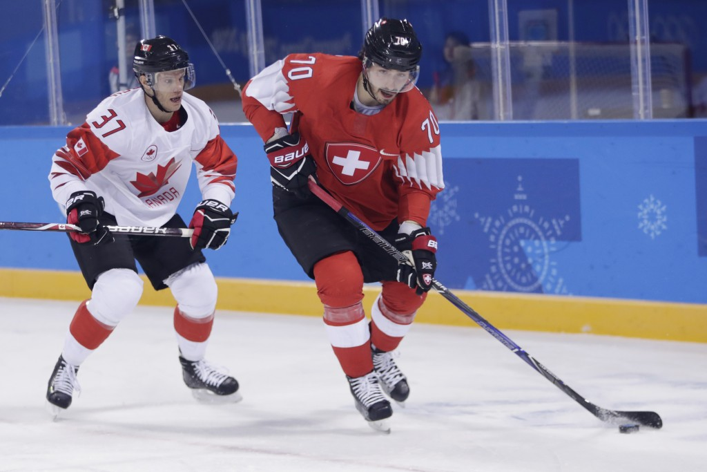 Denis Hollenstein (70), of Switzerland, skates with the puck against Mat Robinson (37), of Canada, during the first period of a preliminary round men'