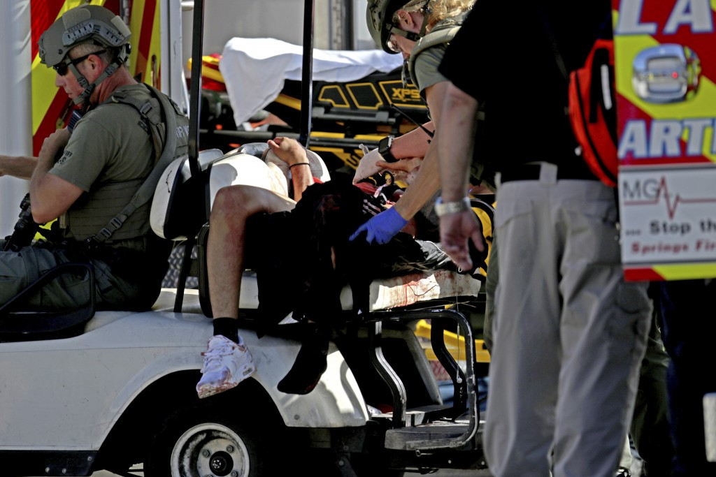 Medical personnel tend to a victim following a shooting at Marjory Stoneman Douglas High School in Parkland, Fla., on Wednesday, Feb. 14, 2018. (John
