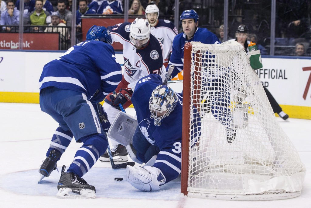 Toronto Maple Leafs goaltender Frederik Andersen makes a save on Columbus Blue Jackets Nick Foligno, center left, during the third period of an NHL ho